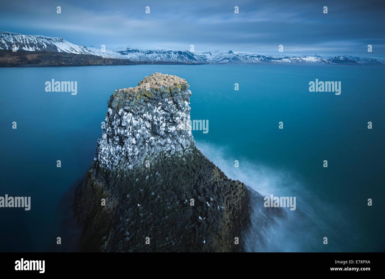 a sea stack streaked with the guano of fulmars and kittiwakes, nr Arnastapi, Snaefellsnes Peninsula, western Iceland - Stock Image