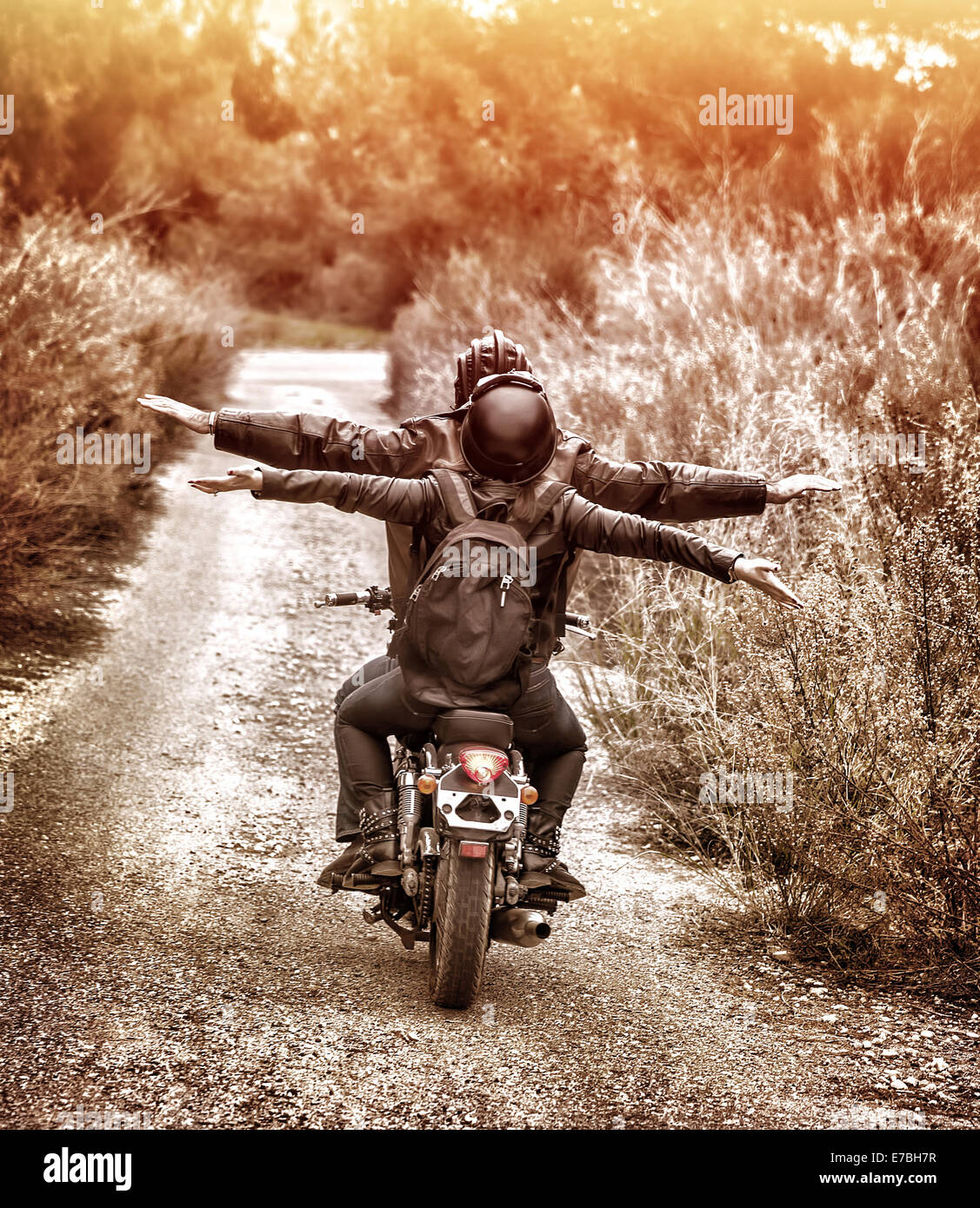 Vintage style image, rear view of two happy bikers riding on the road with raised up hands, active family enjoying - Stock Image