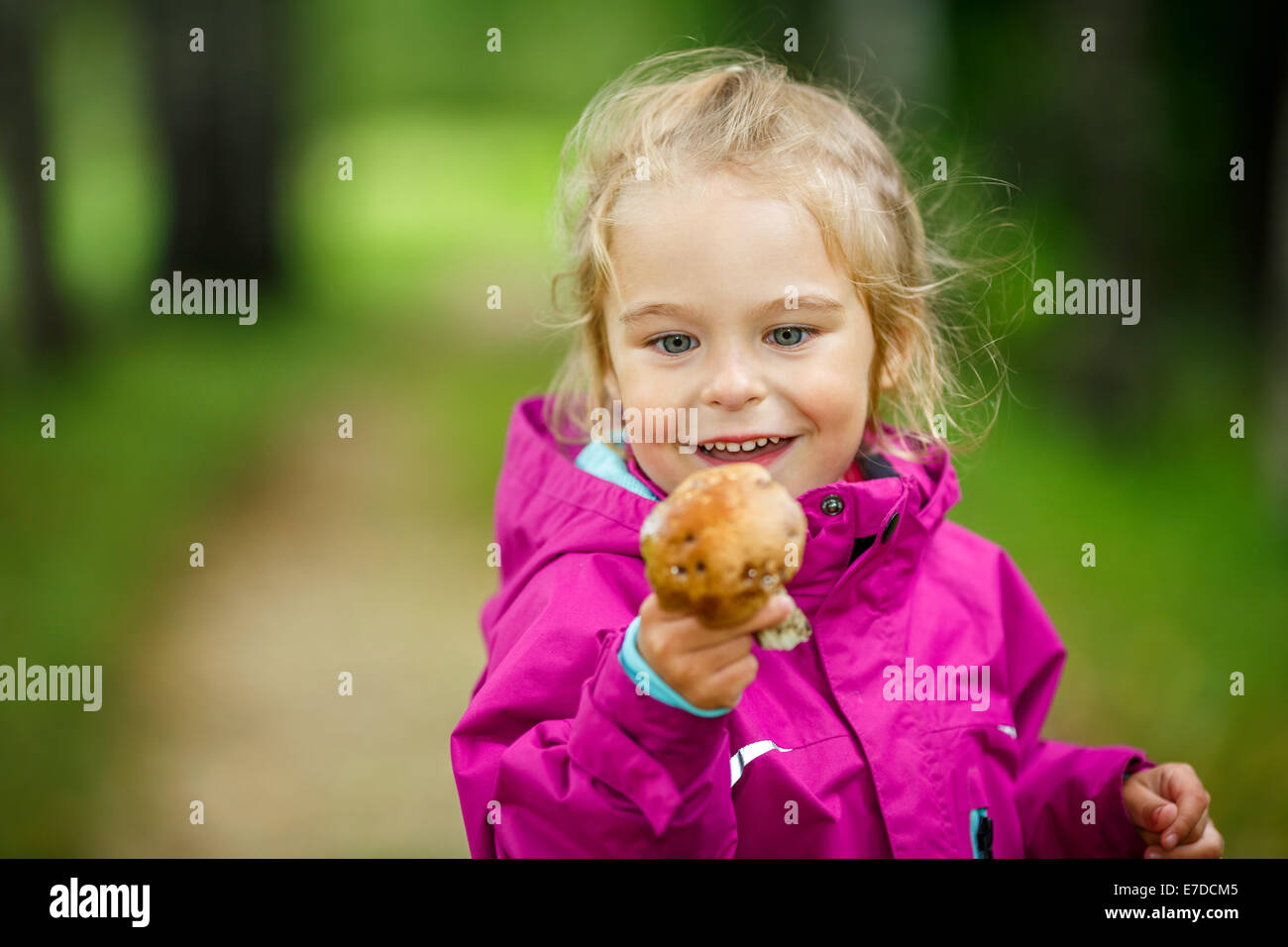 Happy little girl with a mushroom - Stock Image