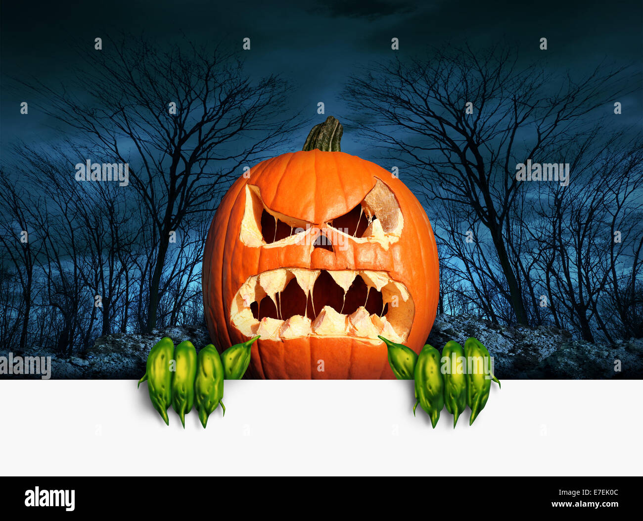 Demon pumpkin sign as an angry scary orange  jack o lantern in a haunted dark autumn forest holding a blank sign - Stock Image