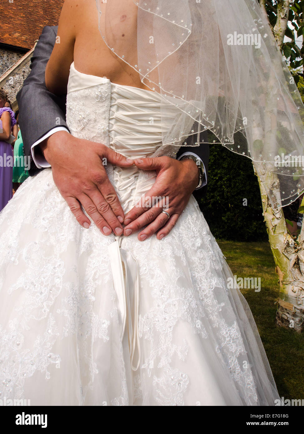 A groom puts his arm around his bride and forms a heart shape with his hands Stock Photo