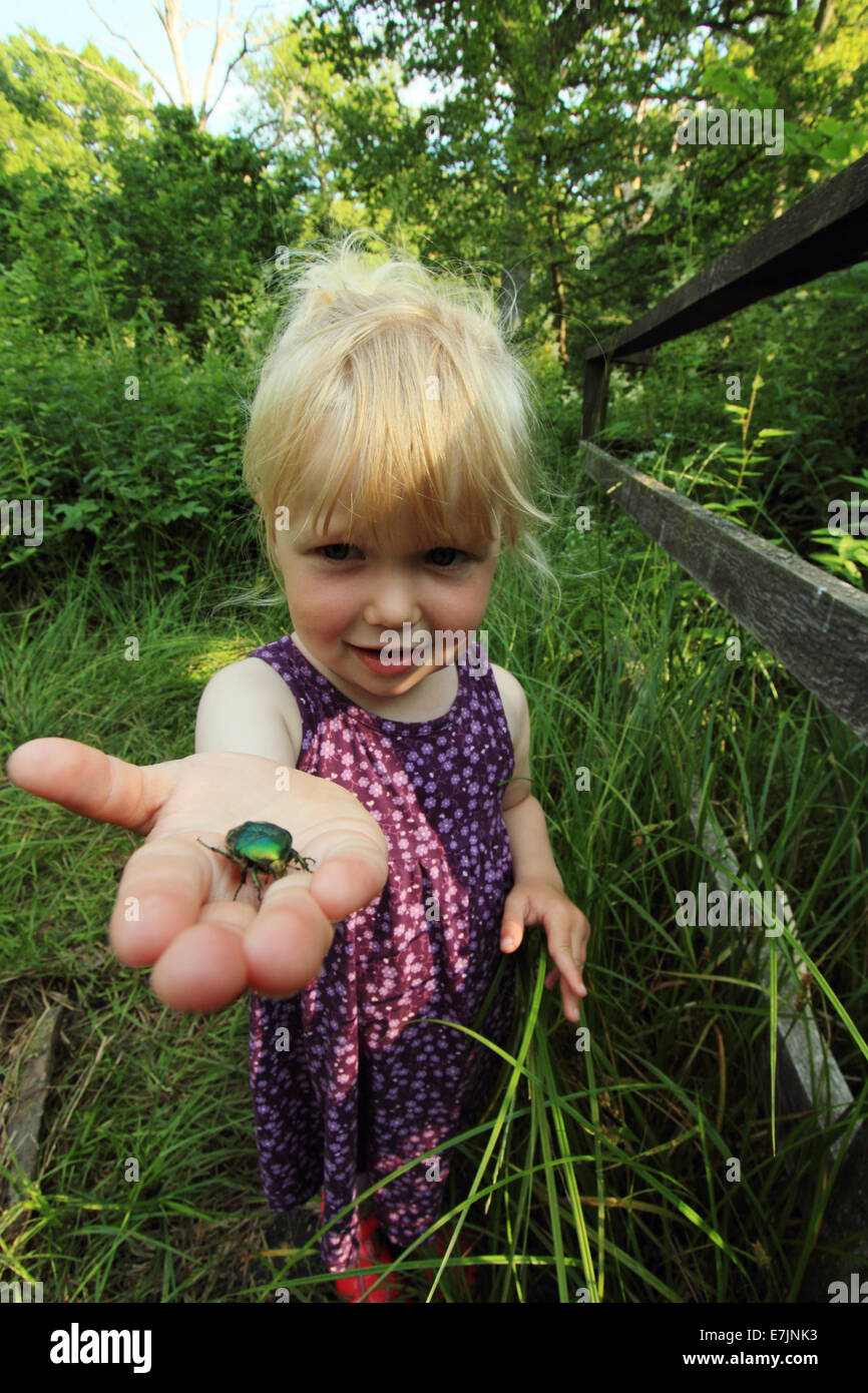 young-girl-holding-a-green-rose-chafer-c