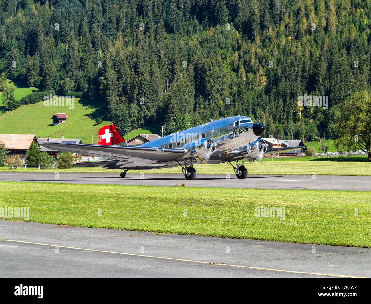 A restored Swissair Douglas DC-3 aircraft on the runway of an airfield between the mountains in central Switzerland - Stock Image