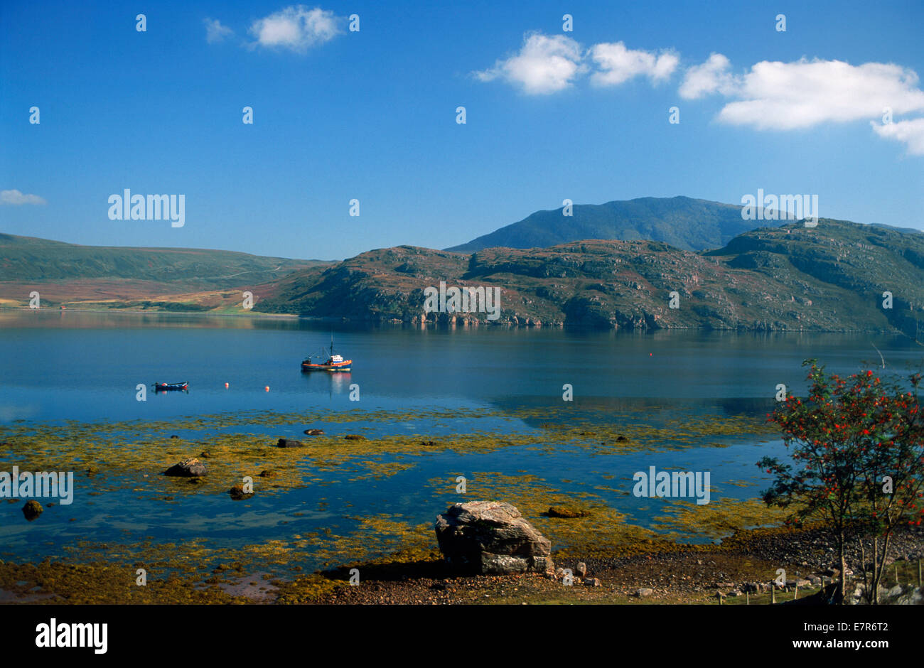Fishermen in small rowboat and lone fishing boat anchored in Lock Broom along the West Coast of Scotland - Stock Image