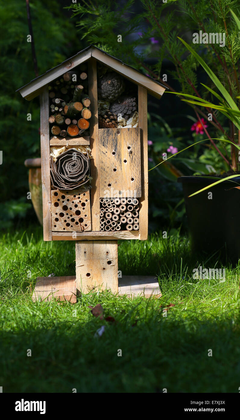 Wooden insect house decorative bug hotel, ladybird and bee home for butterfly hibernation and ecological gardening Stock Photo