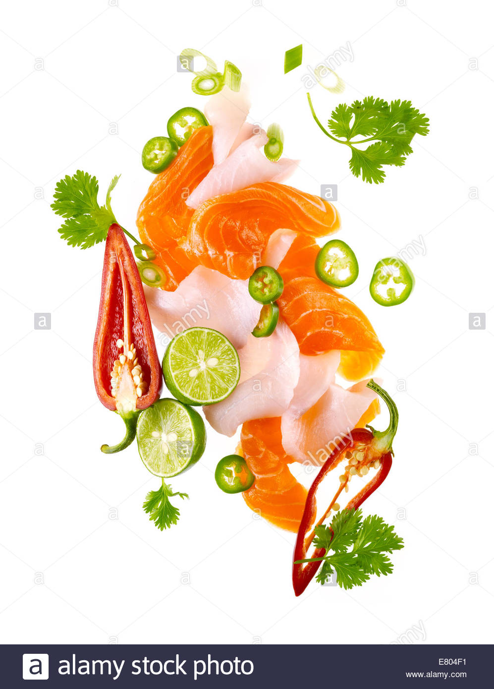 Ceviche of tuna and salmon with finely cut vegetables and garnish on white background - Stock Image
