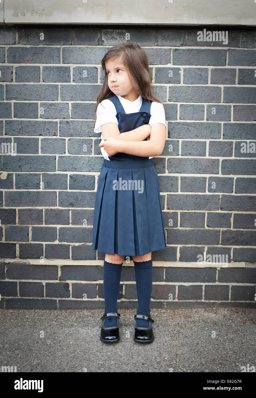 Portrait of girl in playground looking grumpy with arms folded - Stock Image