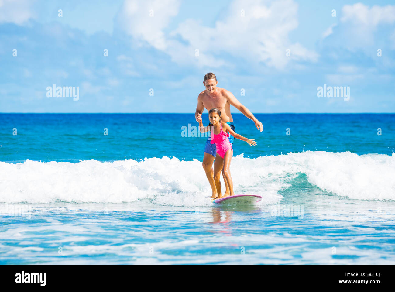 Father and Daughter Surfing Together Catching Wave, Summer Lifestyle Family Concept - Stock Image
