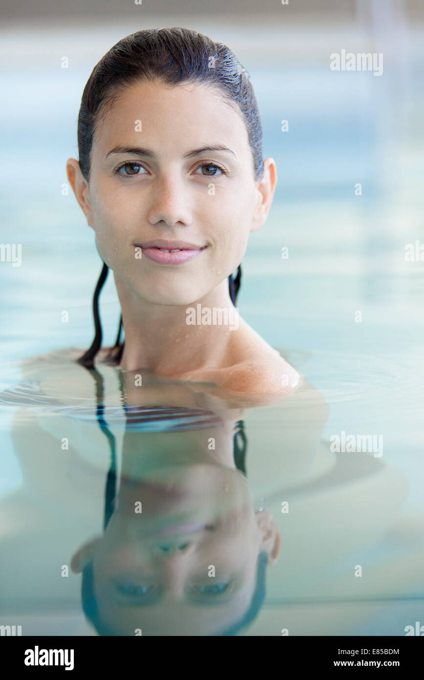 Woman relaxing in swimming pool, portrait - Stock Image
