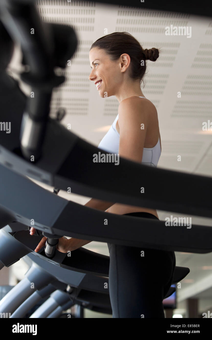 Woman using treadmill in health club - Stock Image