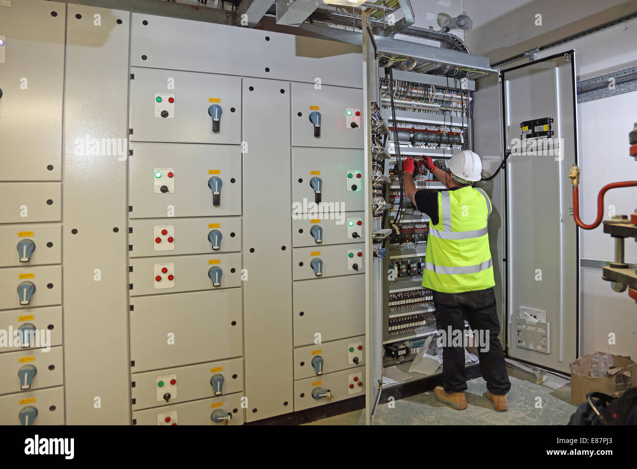 A building services engineer works in an electrical control cabinet ...