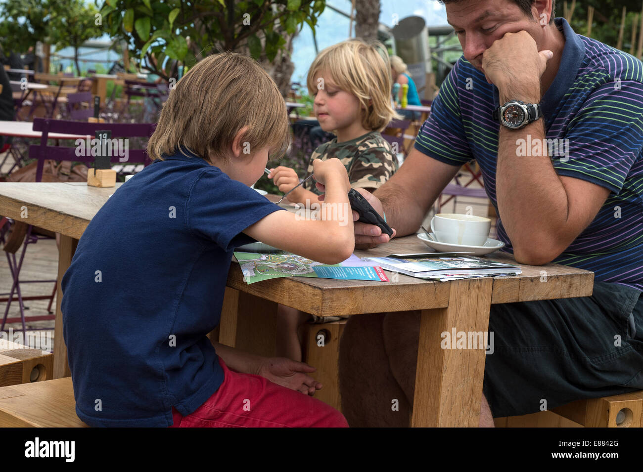 Father with children on holiday. Mobile phone prevents family interaction Cornwall England UK August - Stock Image