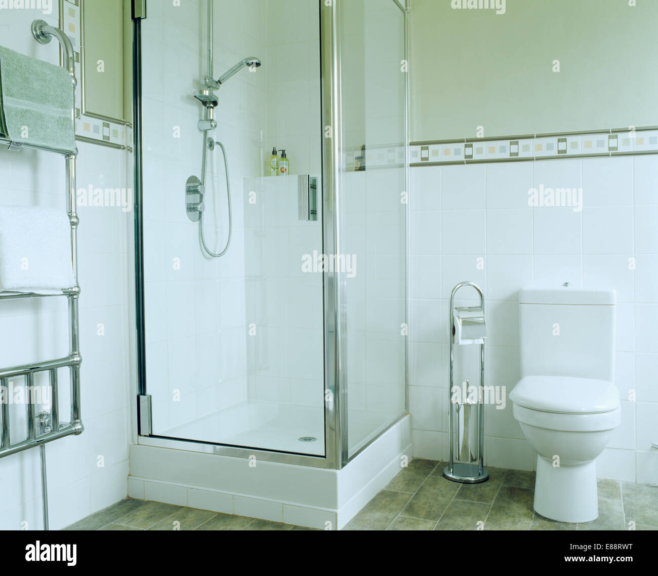 Glass shower cabinet in corner of pale green bathroom with white ...