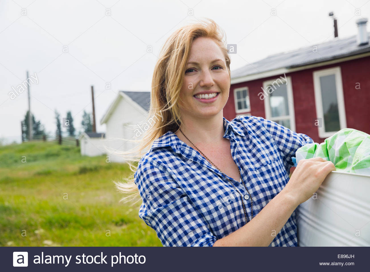 Portrait of smiling woman holding laundry outside house - Stock Image