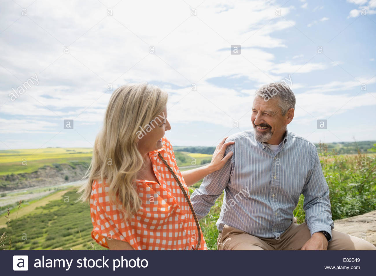 Couple laughing outdoors with countryside in background - Stock Image