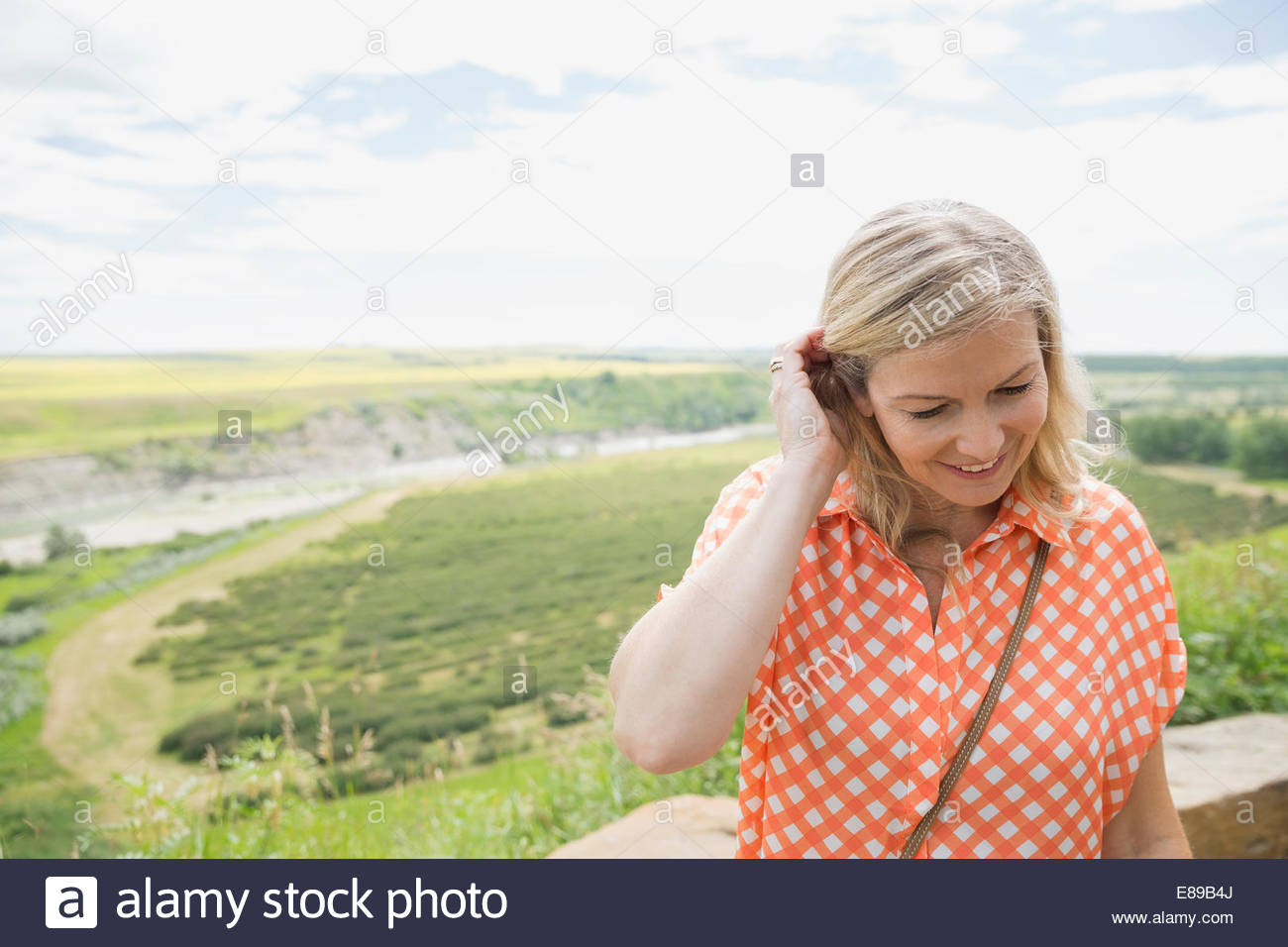 Smiling woman with countryside in background - Stock Image