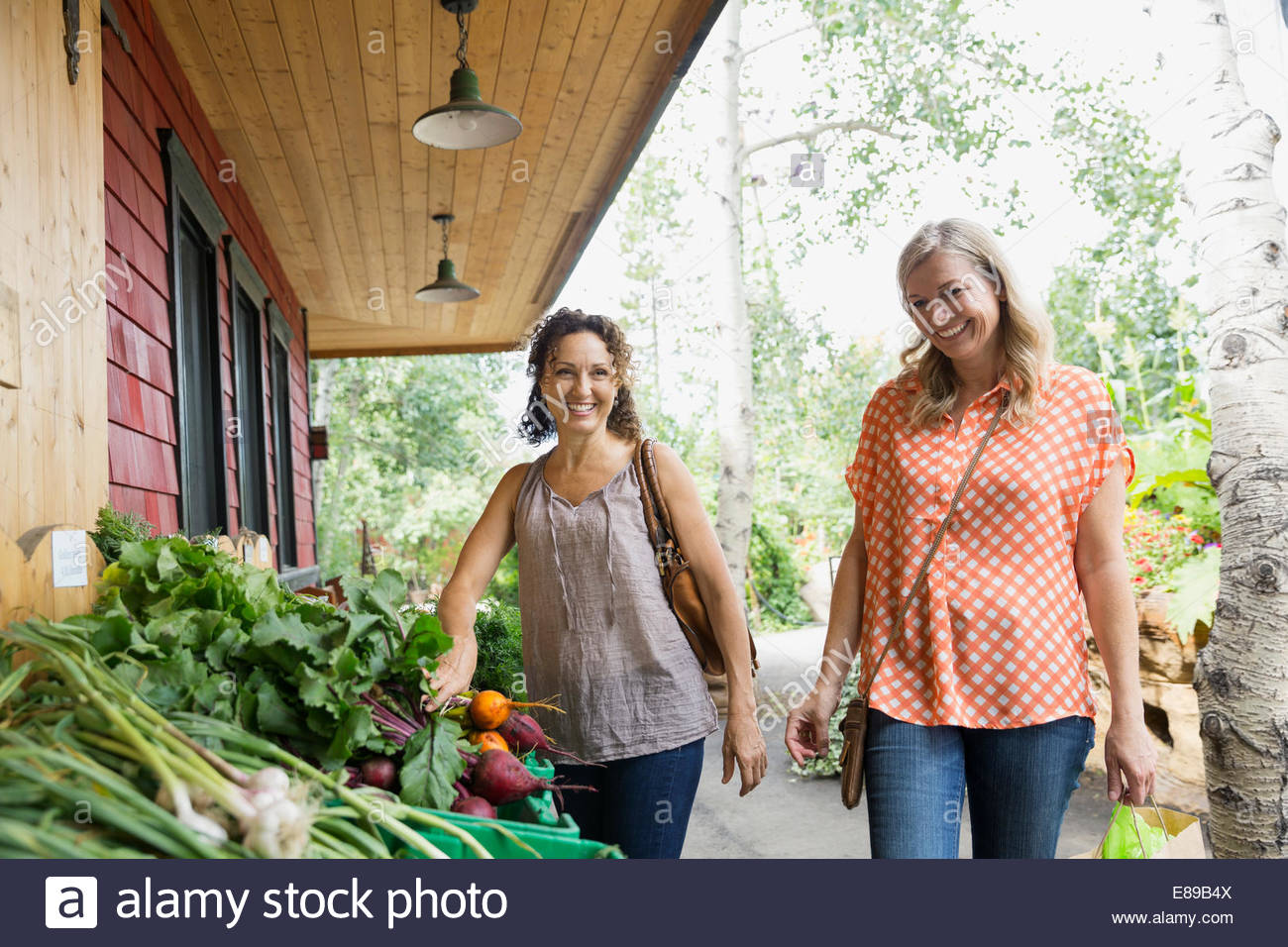 Smiling women shopping for produce outside market - Stock Image