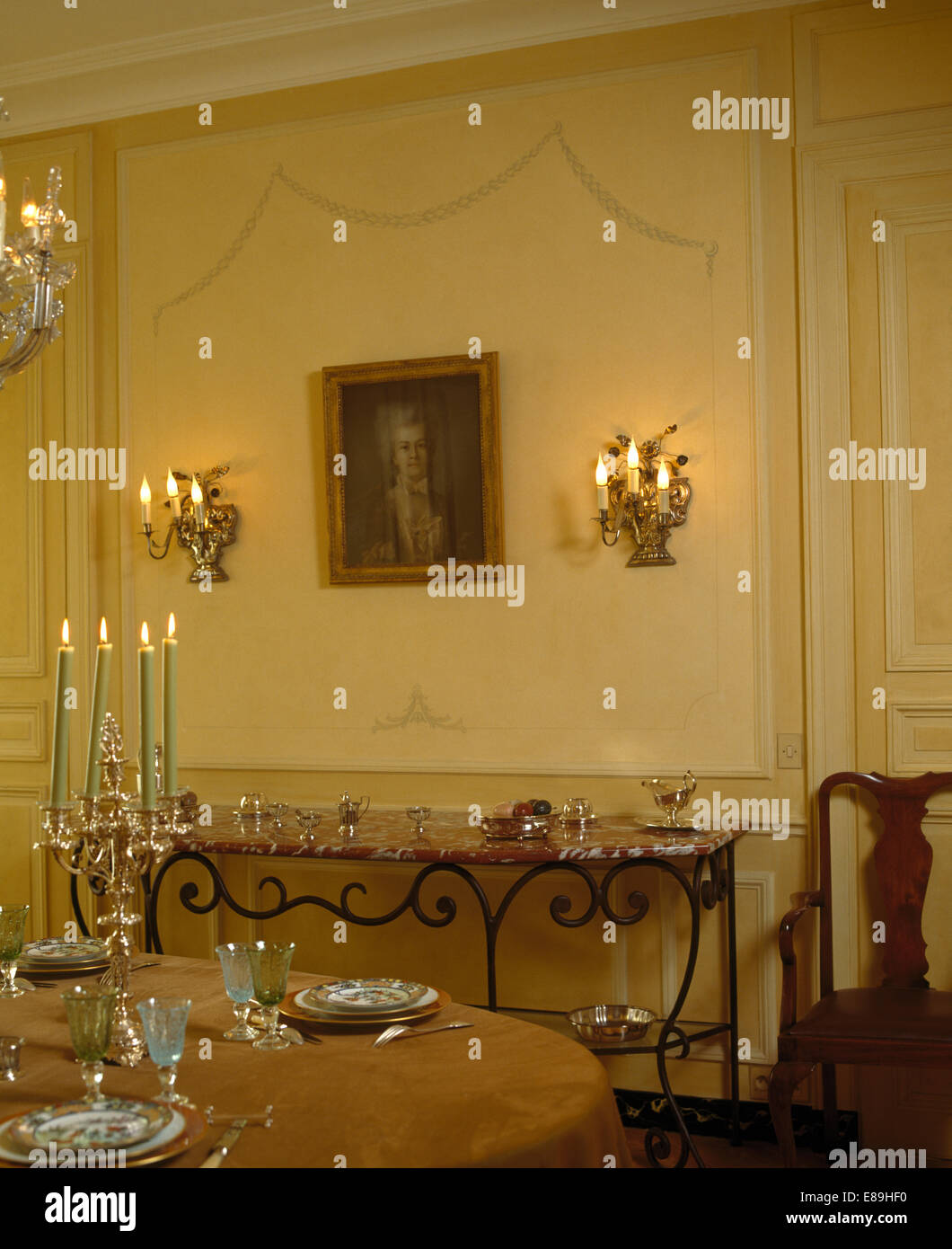 Lighted wall lights on either side of framed portrait in French ...