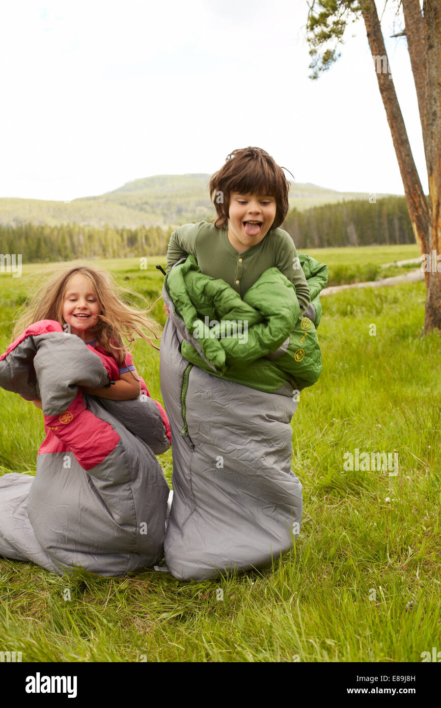 Boy and girl sack racing in sleeping bags - Stock Image