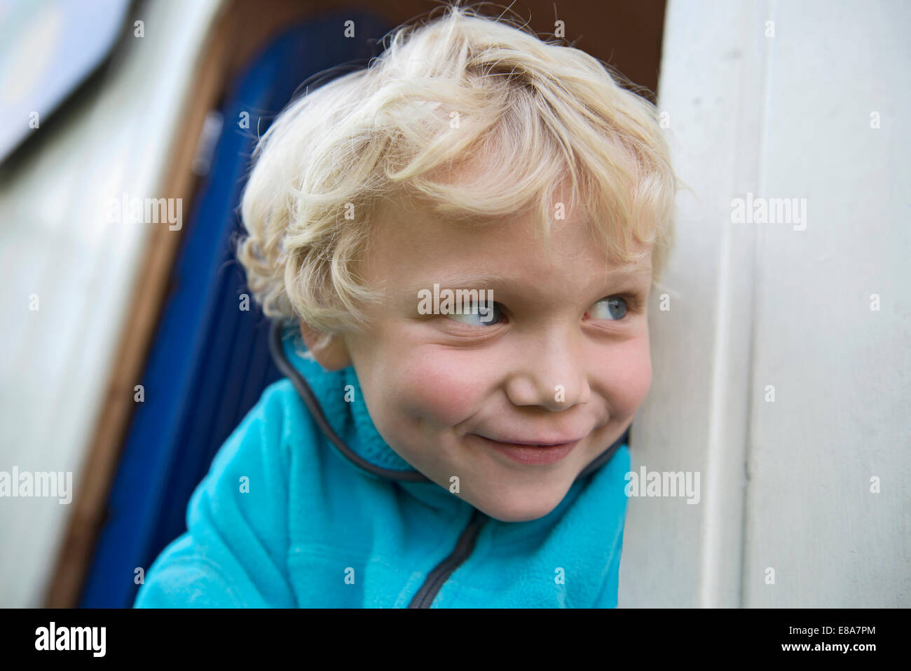 Close up portrait of young cheeky blonde boy - Stock Image