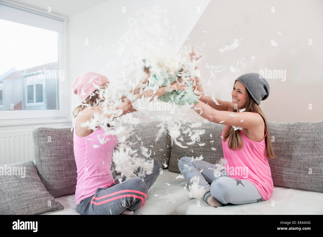 Two female friends sitting on couch at home having pillow fight - Stock Image