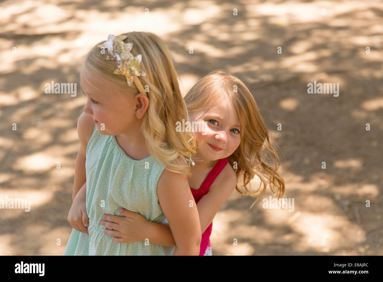 Young girl hiding behind sister in park - Stock Image