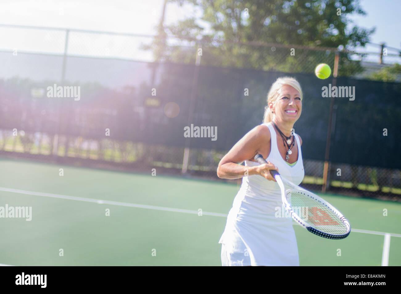 Smiling mature woman playing tennis - Stock Image