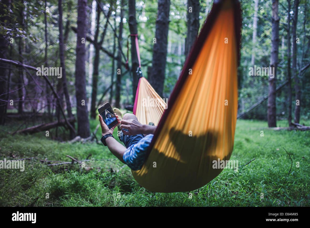 Hiker lying in hammock in forest using digital device - Stock Image