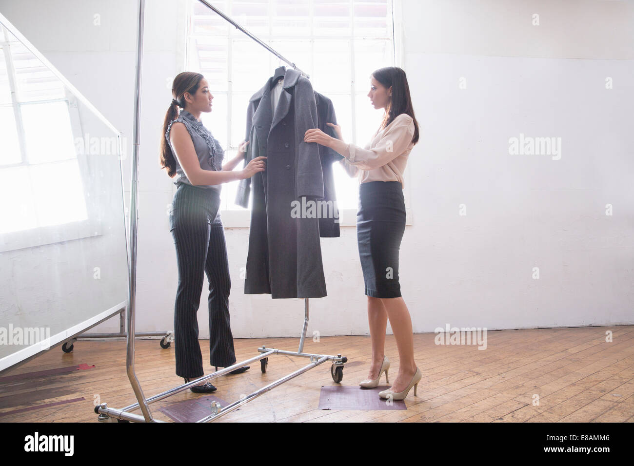 Businesswomen choosing smart clothes from clothes rail - Stock Image