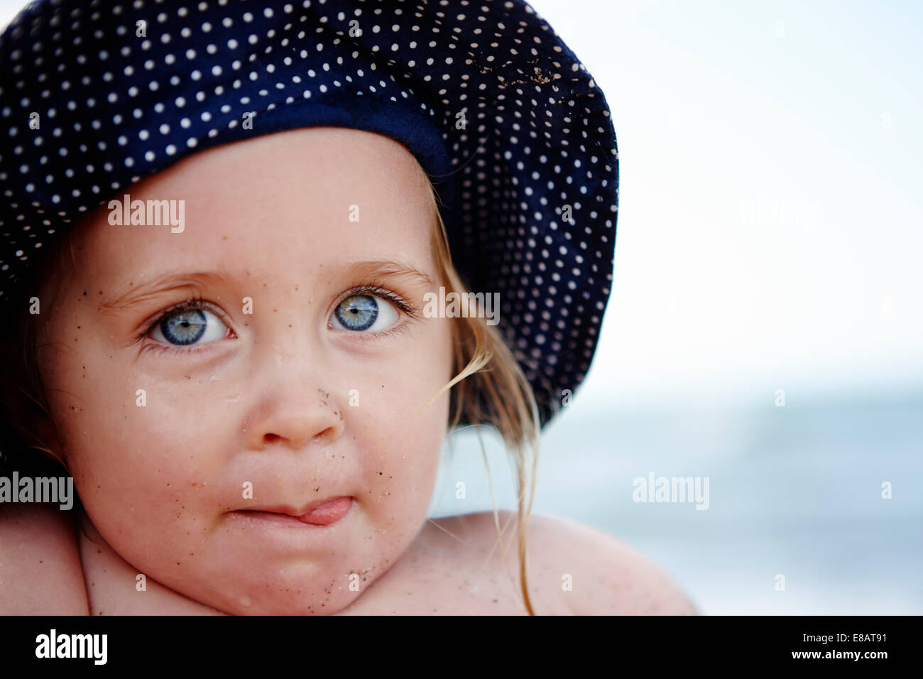 Young girl wearing spotty hat, portrait - Stock Image