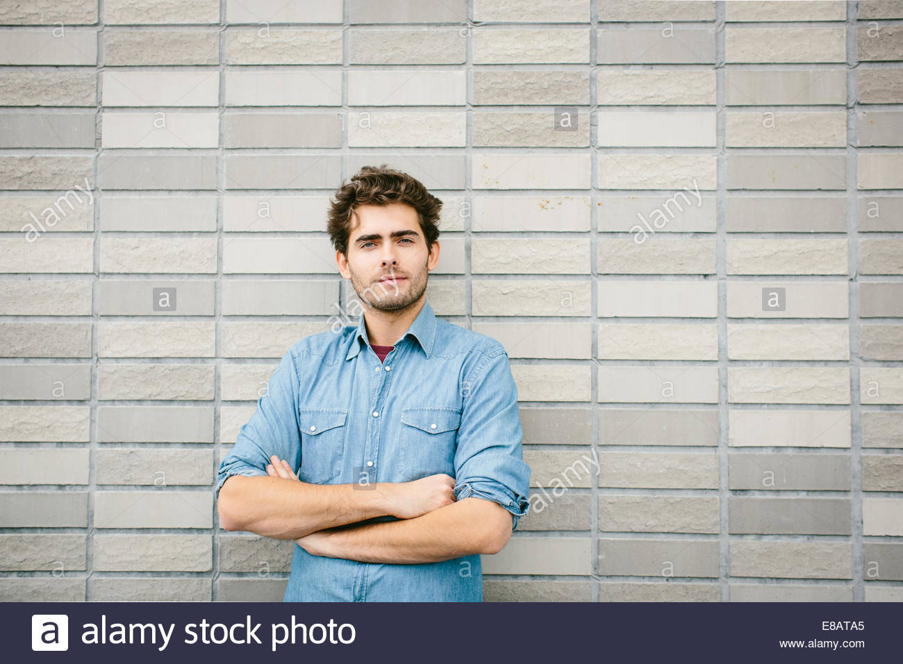 Young man wearing denim shirt by brick wall, portrait - Stock Image