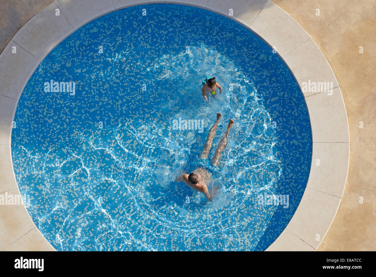 Overhead view of man and toddler daughter in swimming pool - Stock Image