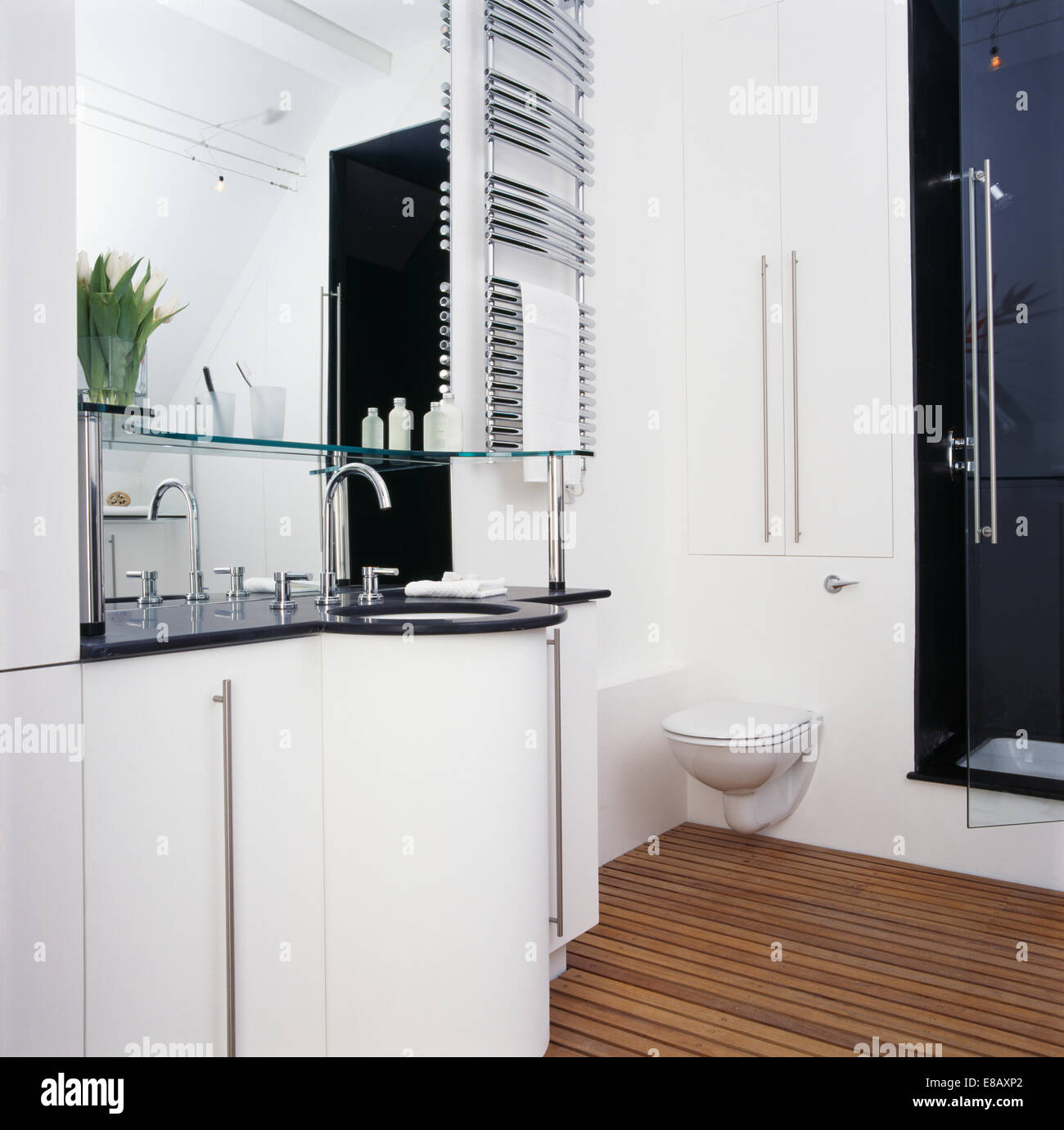 Slatted wooden flooring in modern white bathroom with wall mounted ...