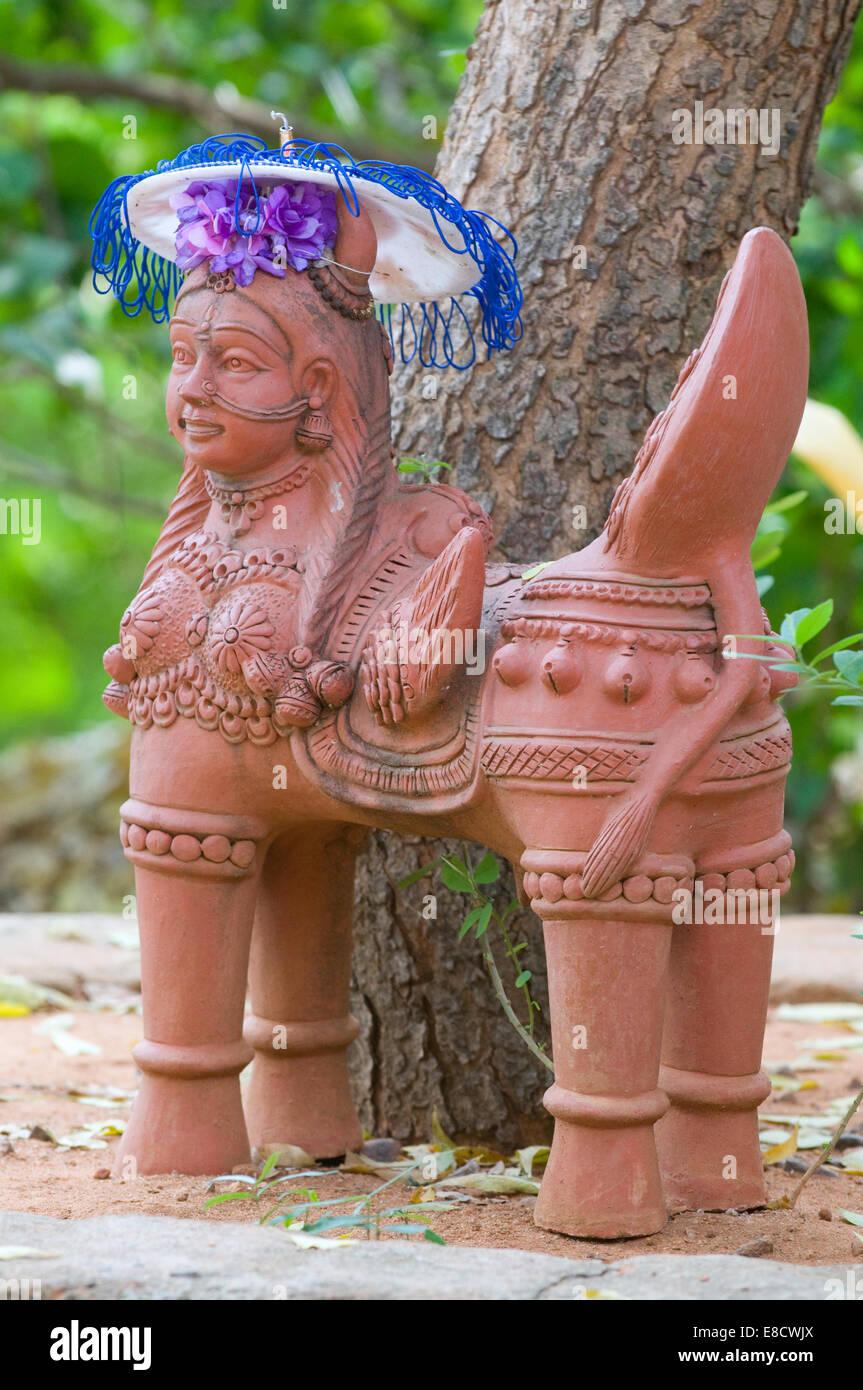 Clay sculpture of mythic Hindu temple female angelic four legged creature sat under tree with ornate parasol Tiruvannamalai - Stock Image