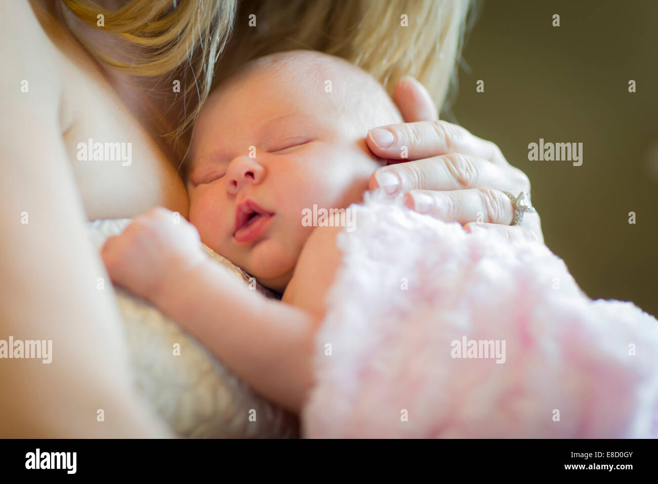 Gentle Hands of Mother Holding Her Precious Newborn Baby Girl. - Stock Image