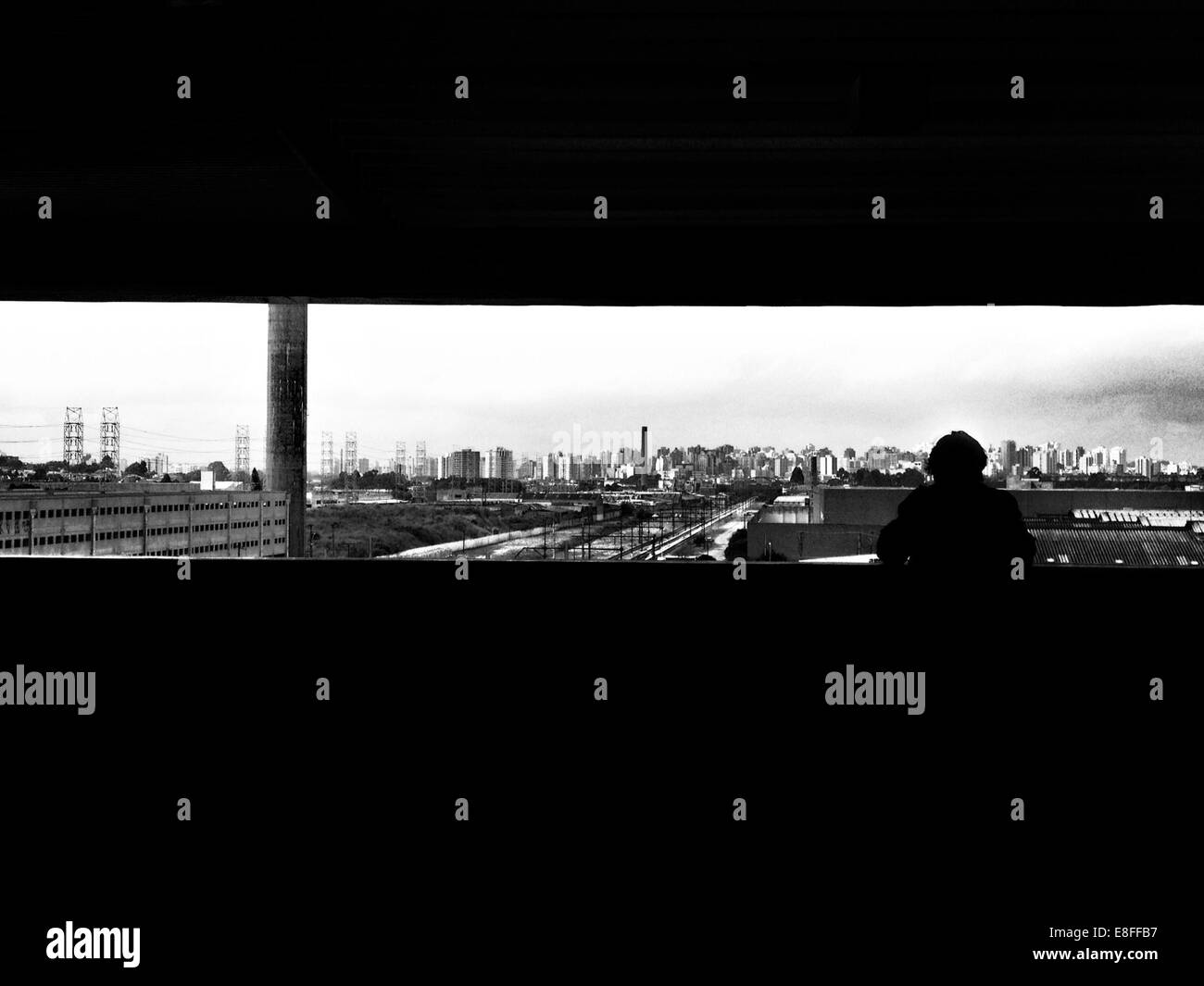 Silhouette of a person looking at city skyline, Sao Paulo, Brazil - Stock Image