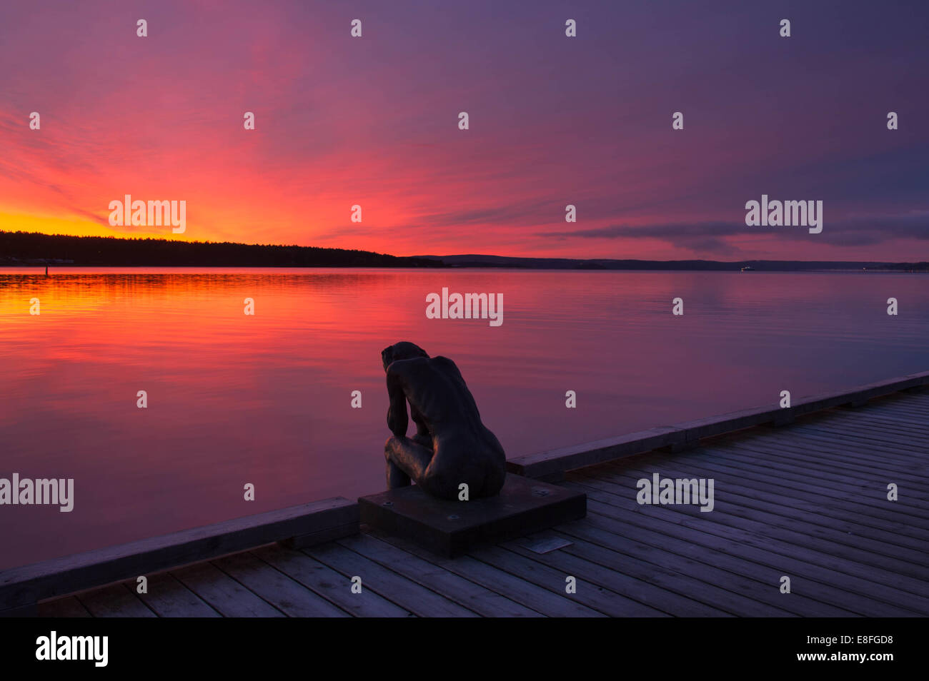 Statue overlooking fjord at sunset - Stock Image
