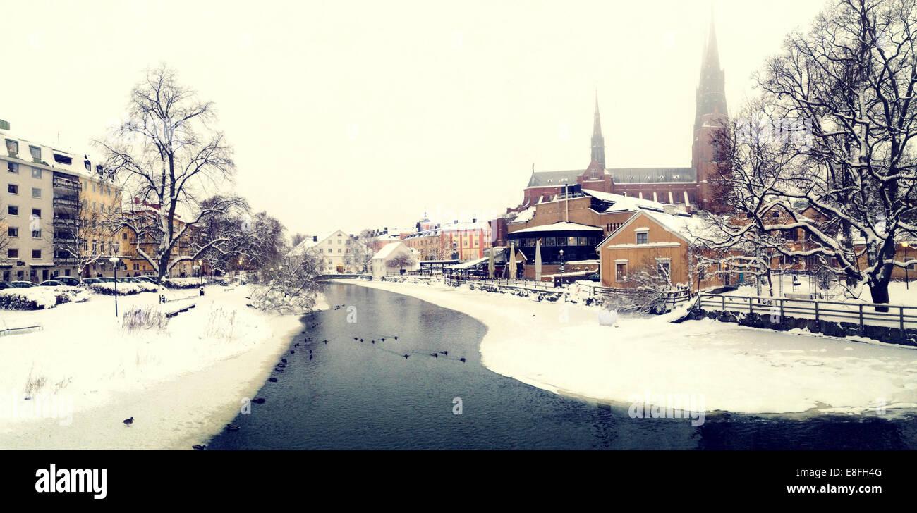 Sweden, Svealand, Uppsala, Fyris river and Uppsala Cathedral (Domkyrkan) in winter - Stock Image