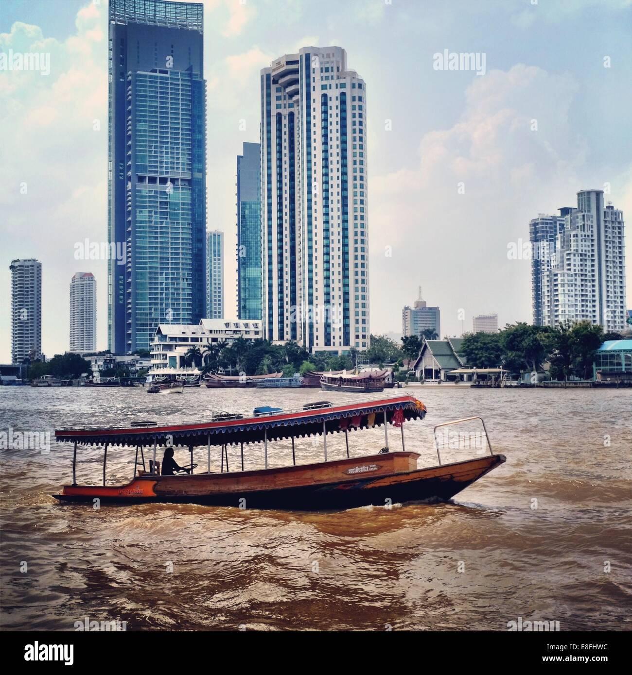 Thailand, Bangkok, River boat and cityscape - Stock Image