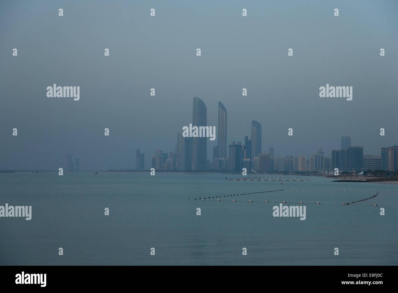 United Arab Emirates, Abu Dhabi, Skyline at dusk - Stock Image