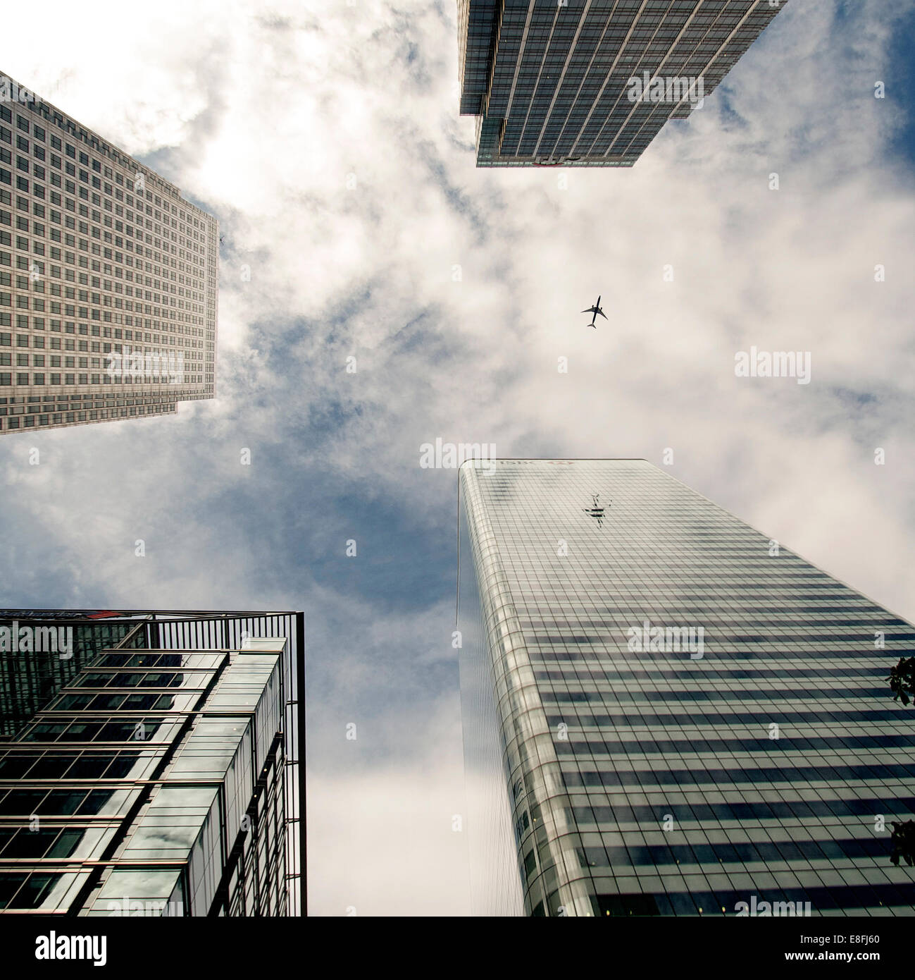 Plane flying past skyscrapers, Canada Square, London, England, UK - Stock Image
