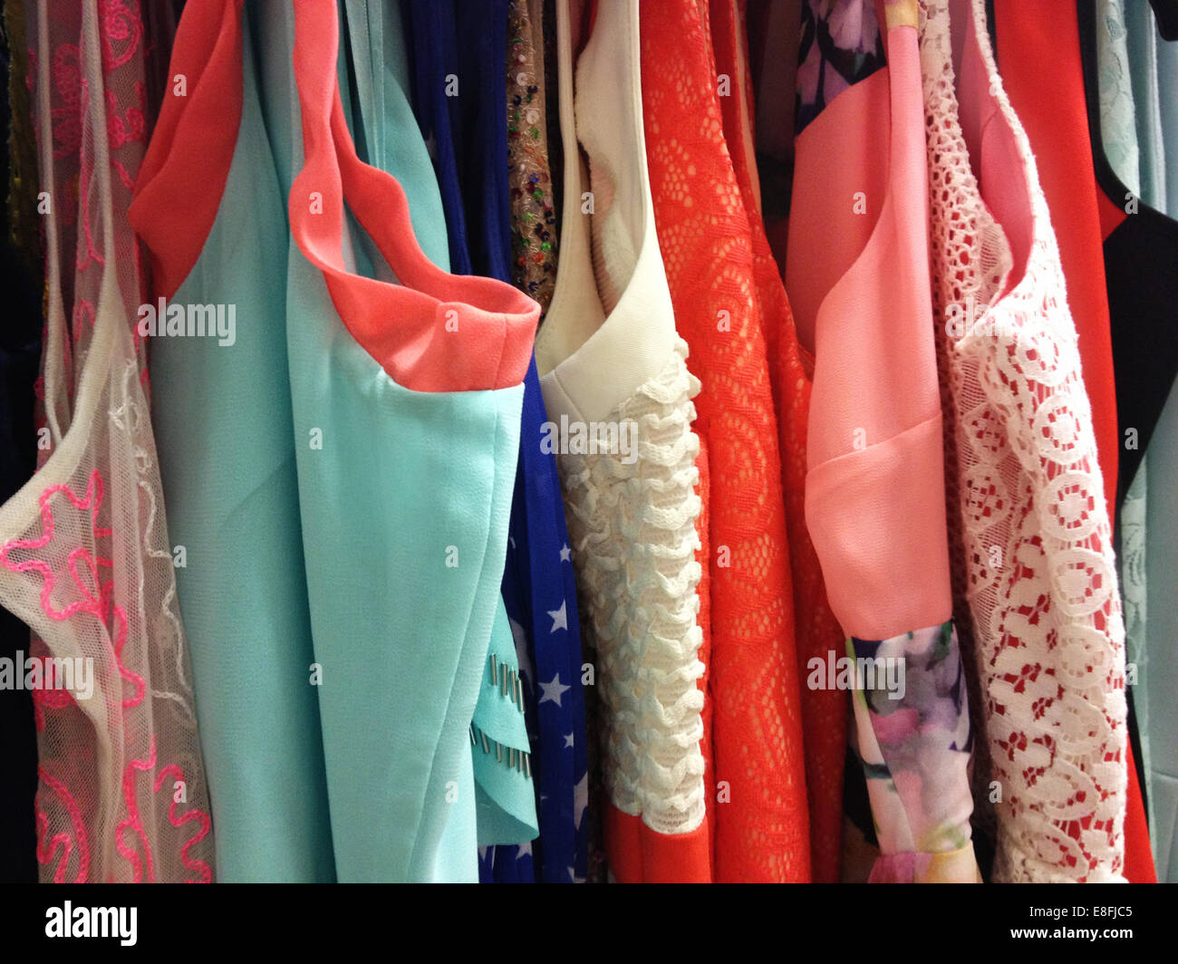Woman's clothes hanging on rail - Stock Image