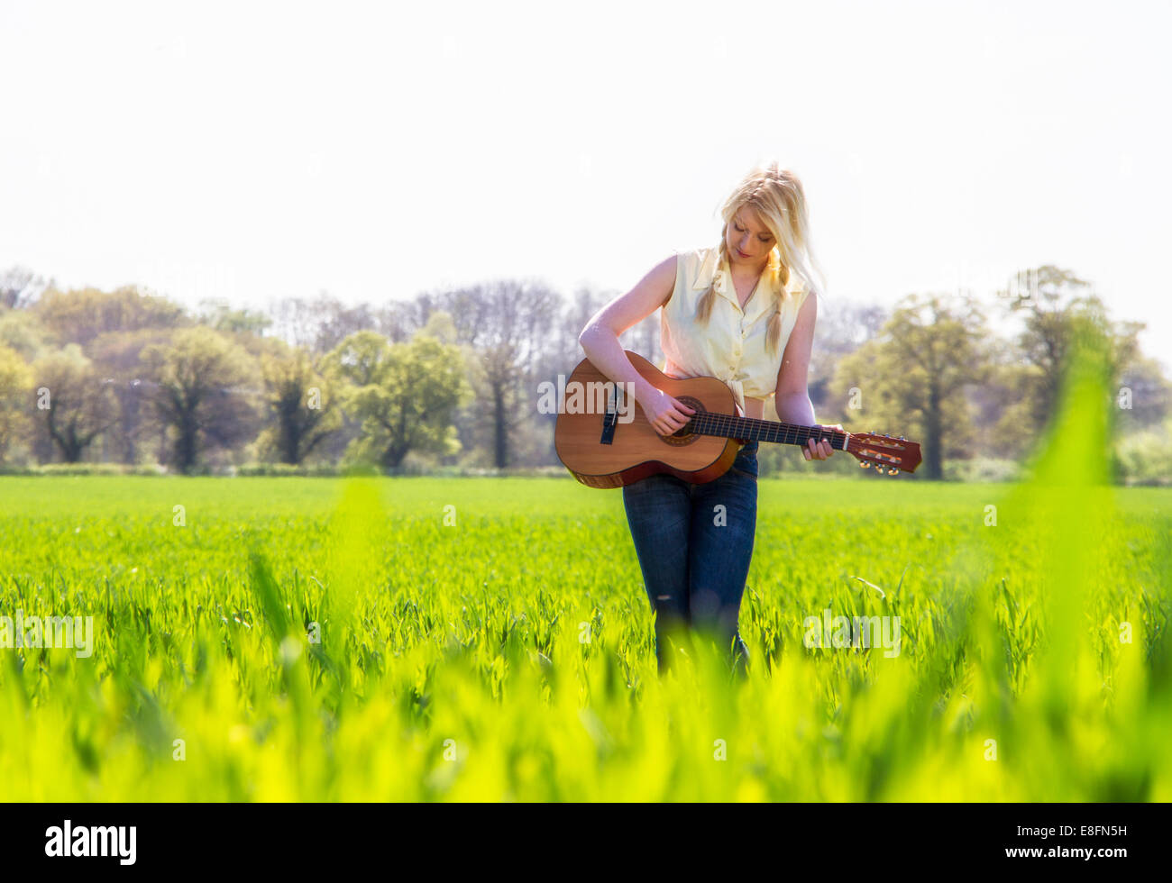 Female country singer in grass field - Stock Image