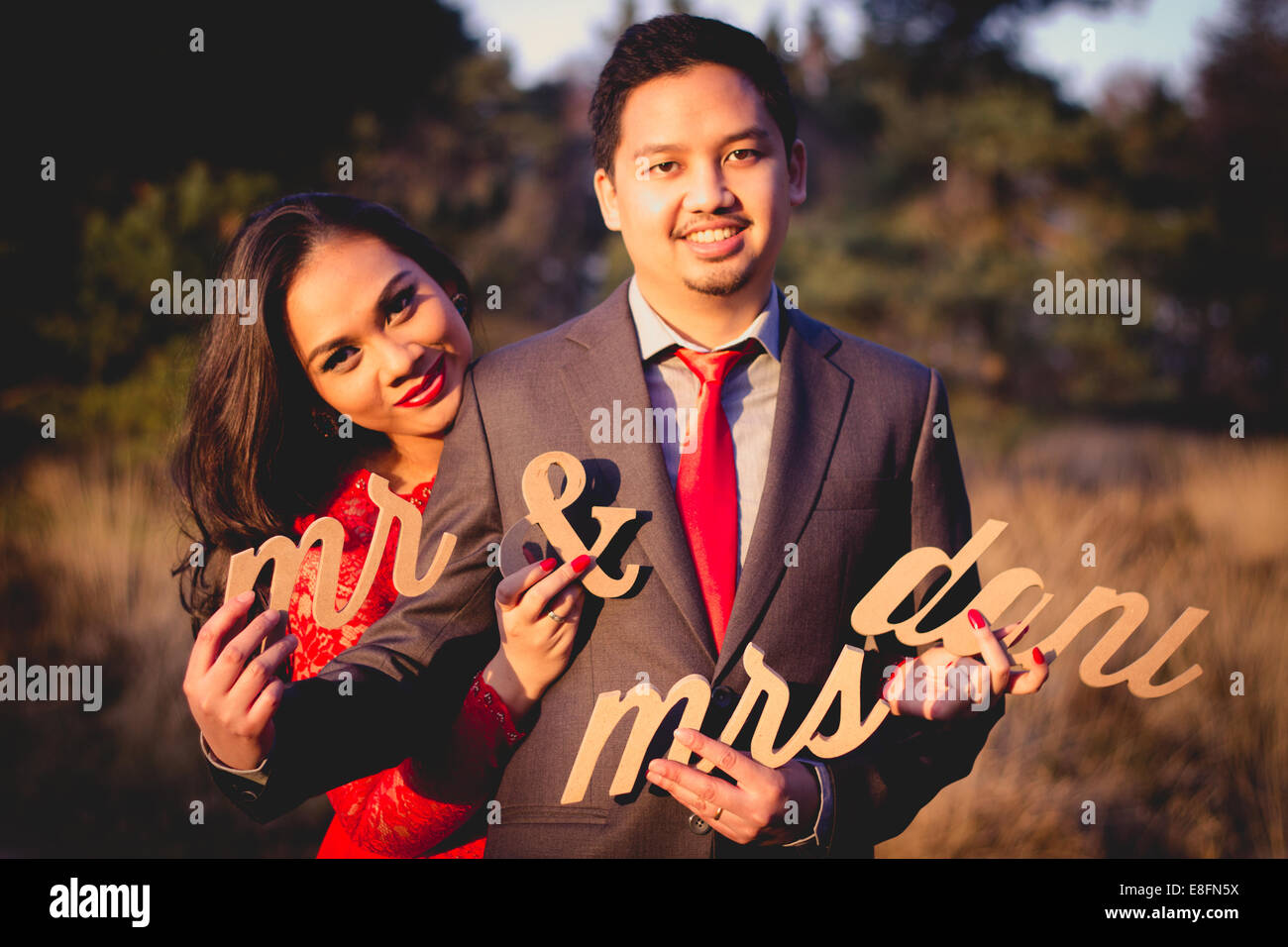 Netherlands, Portrait of couple holding cut out letters - Stock Image