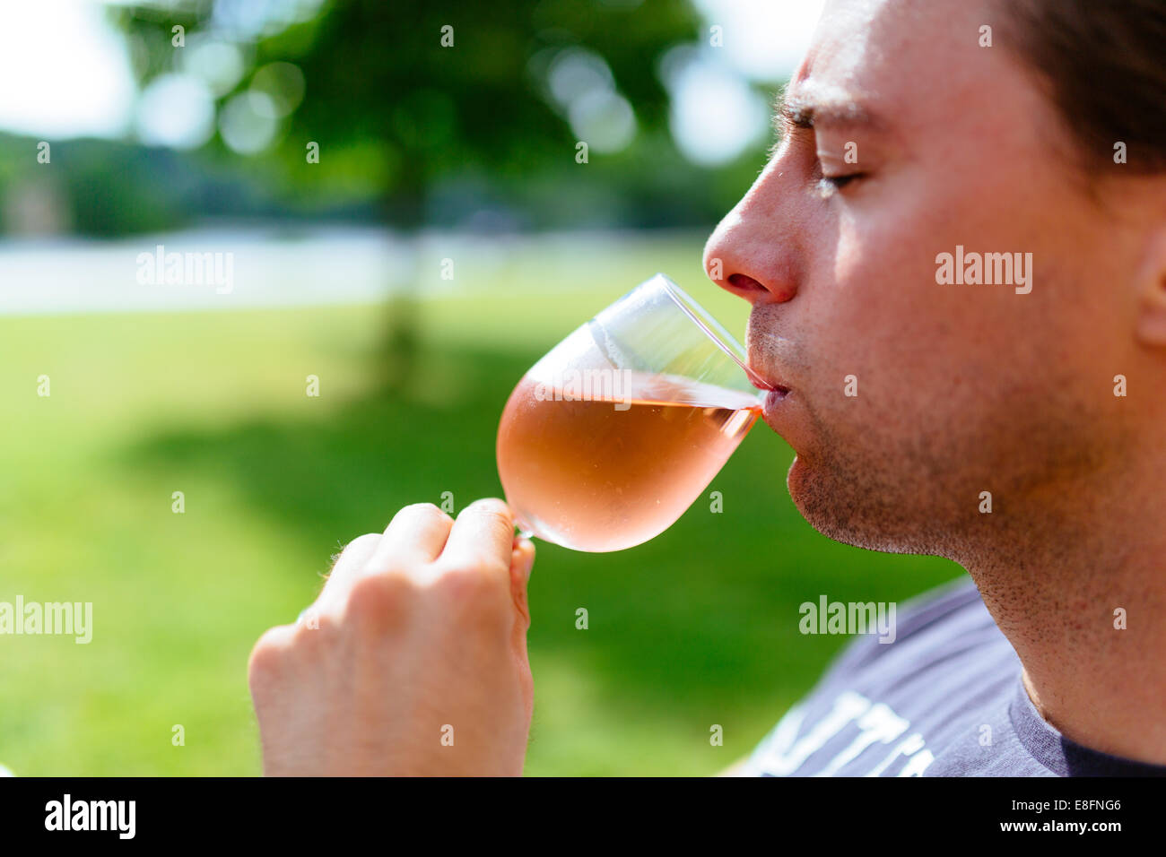 Man drinking glass of chilled summer wine - Stock Image