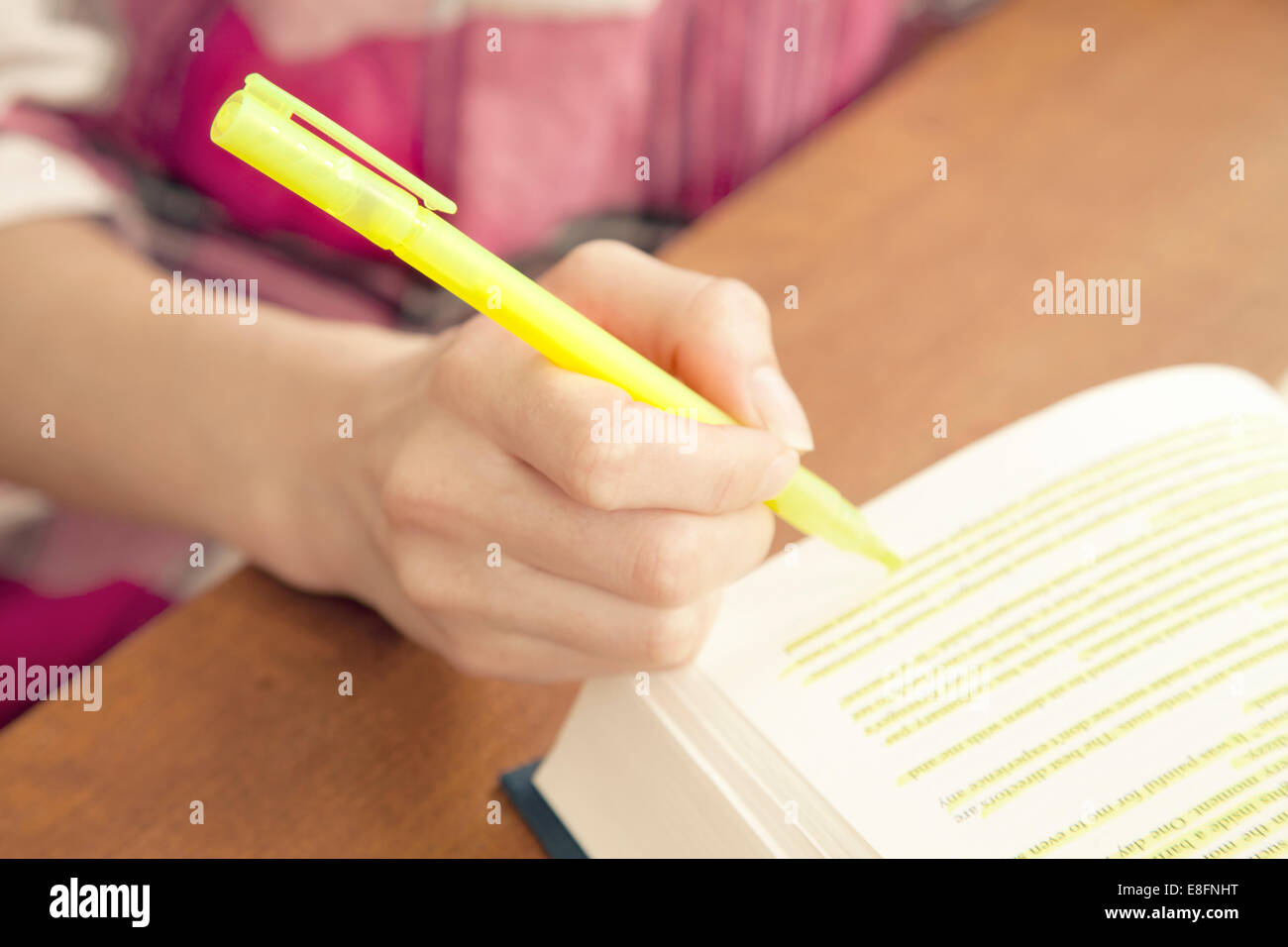Woman highlighting a passage in a book Stock Photo