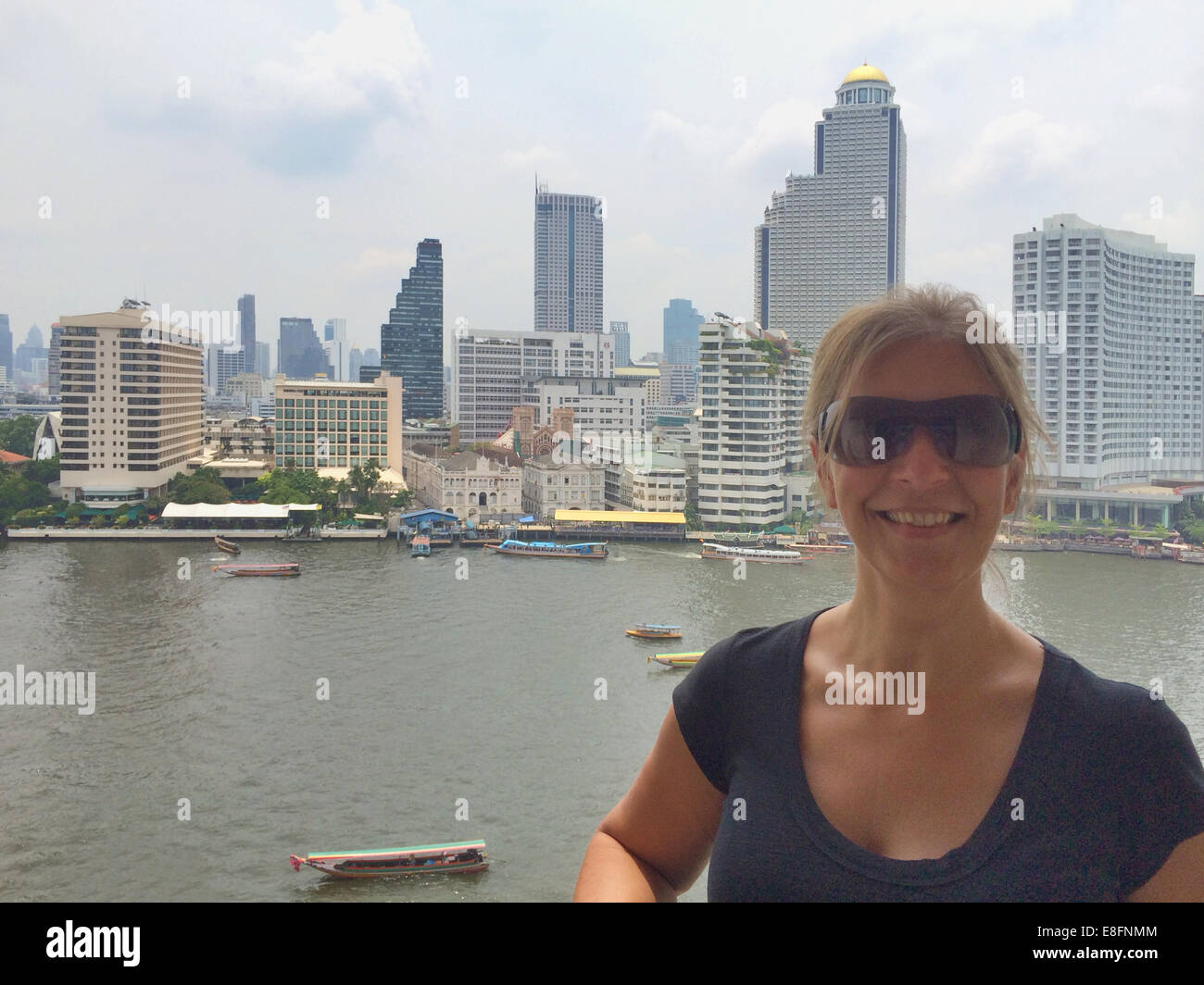 Thailand, Bangkok, Portrait of woman with cityscape in background - Stock Image
