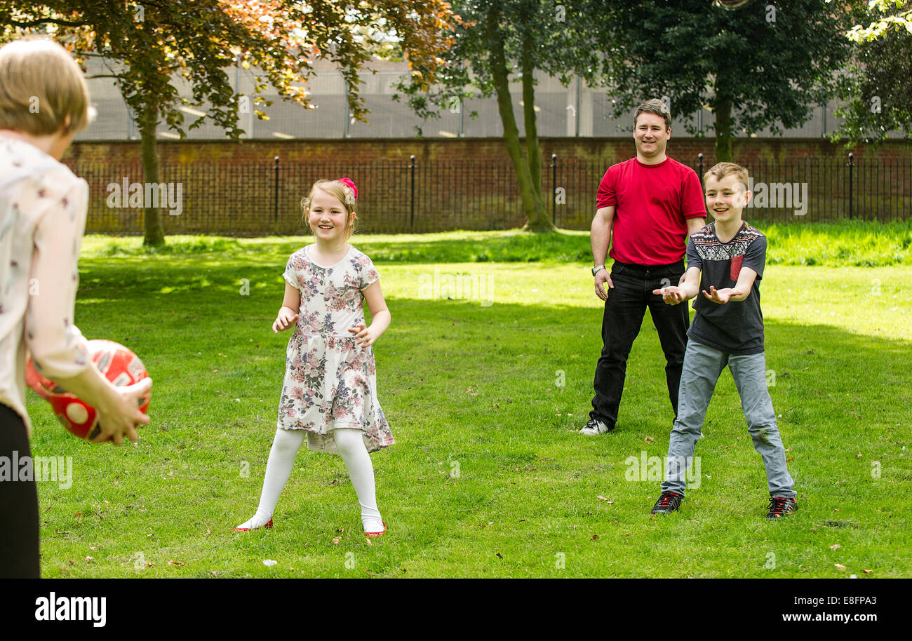 UK, West Midlands, Family with children (8-9), (10-11) ball game - Stock Image