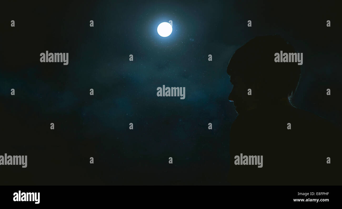 Silhouette of boy (12-13) in moonlight - Stock Image