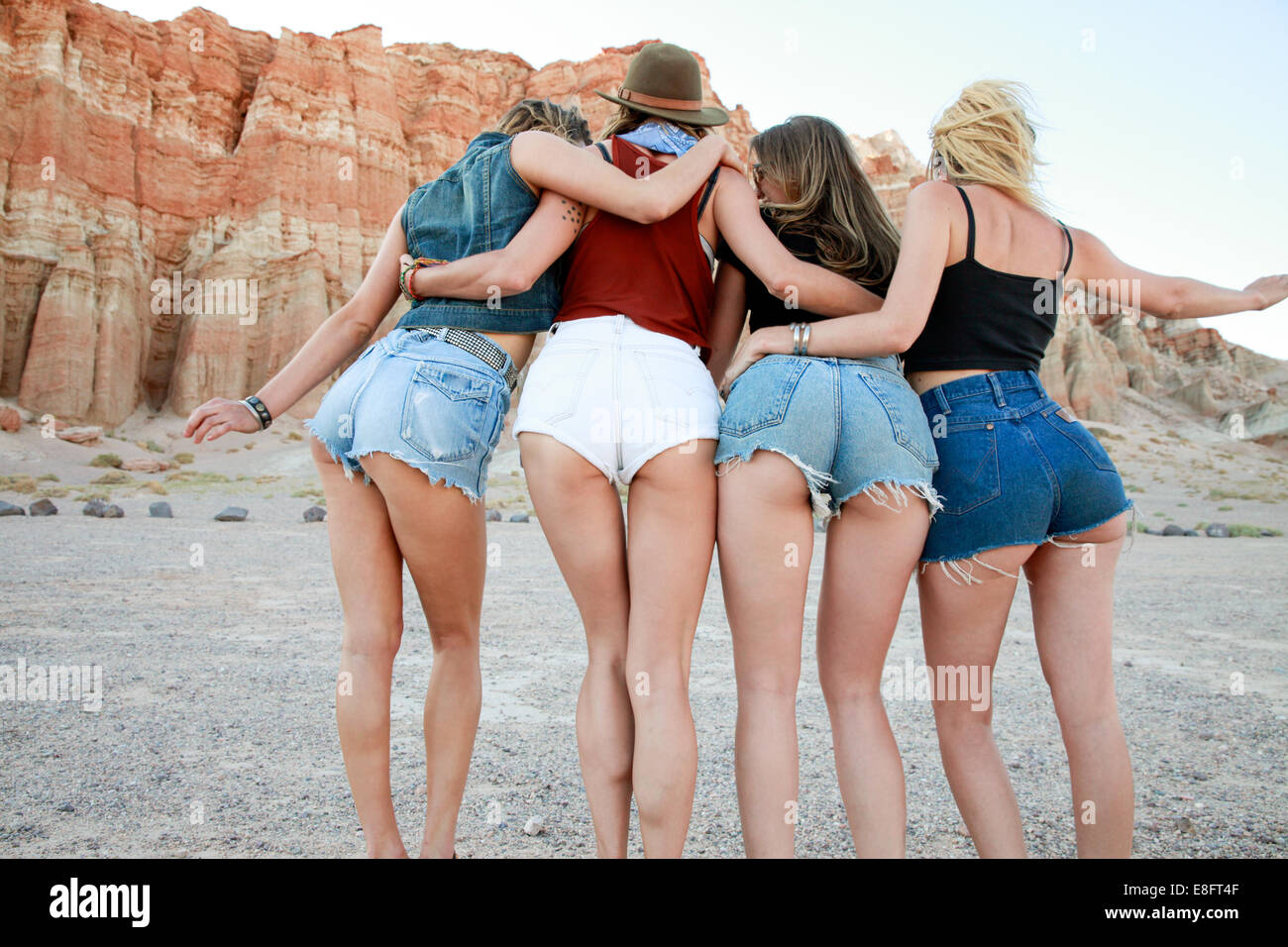Rear view of four women wearing denim shorts - Stock Image